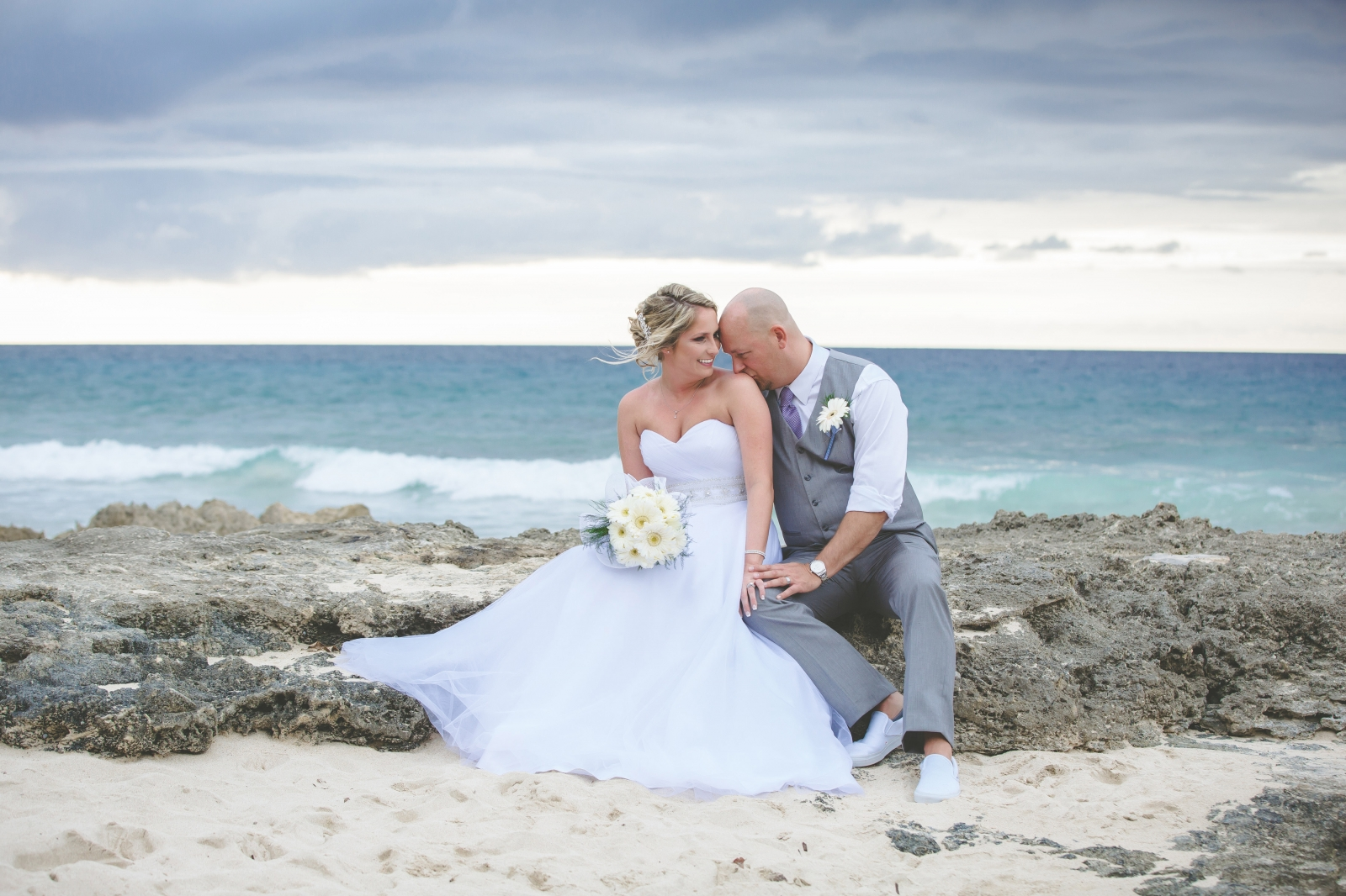 St. Croix wedding couple on beach sitting on rock