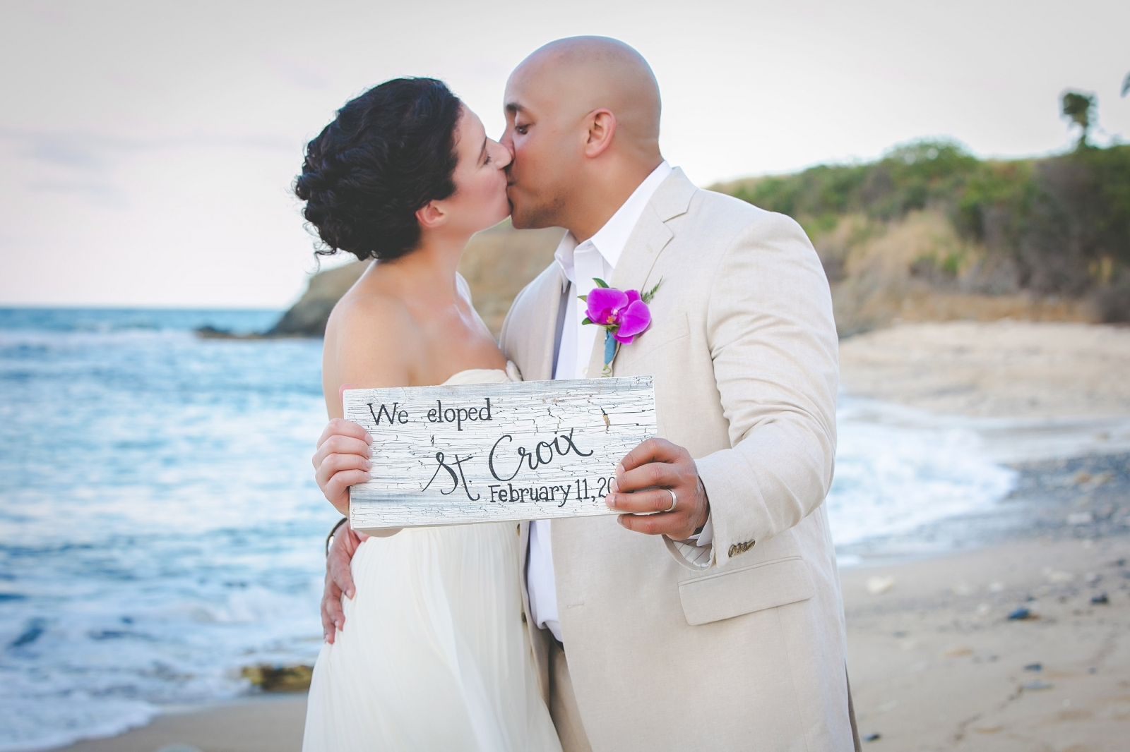 St. Croix wedding couple kissing on beach holding a wedding sign