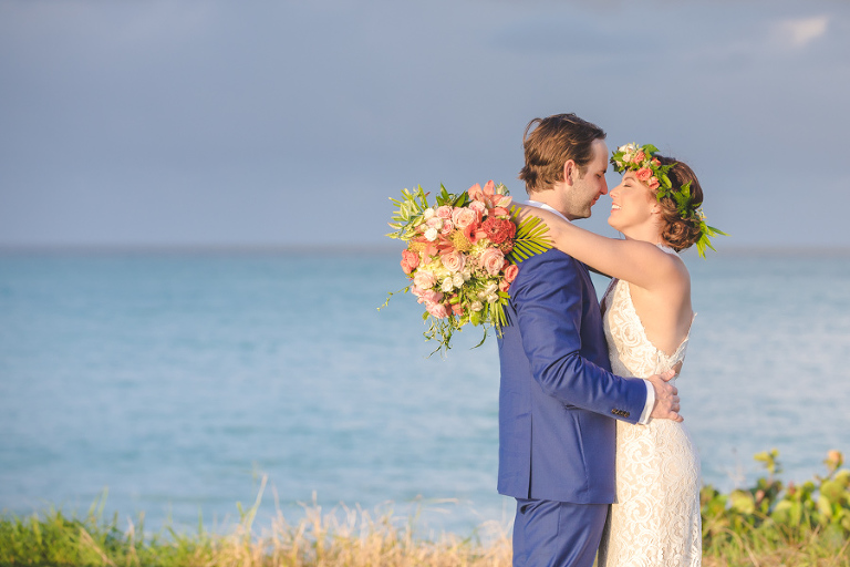 St. Croix bride and groom kissing on hillside overlooking the ocean