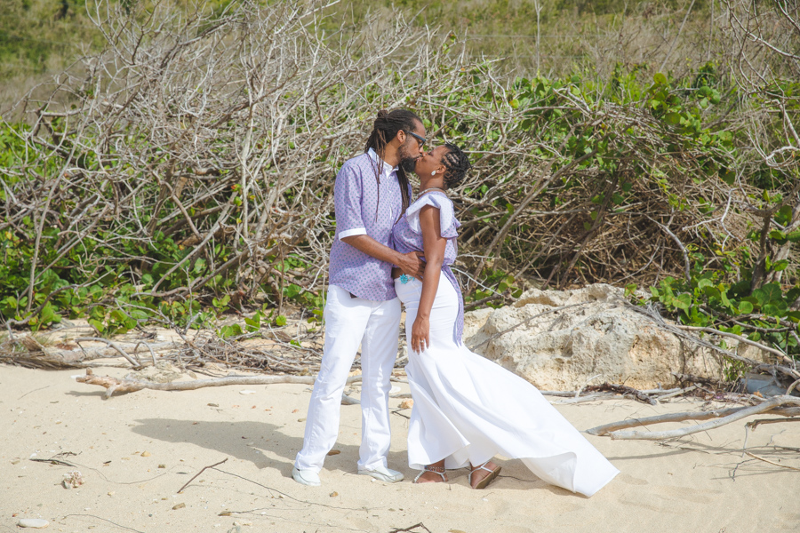 St. Croix bride and groom kissing on rocky beach with large bushes in the background