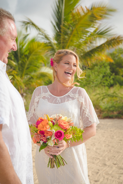 St. Croix bride laughing on beach with bouquet bouquet