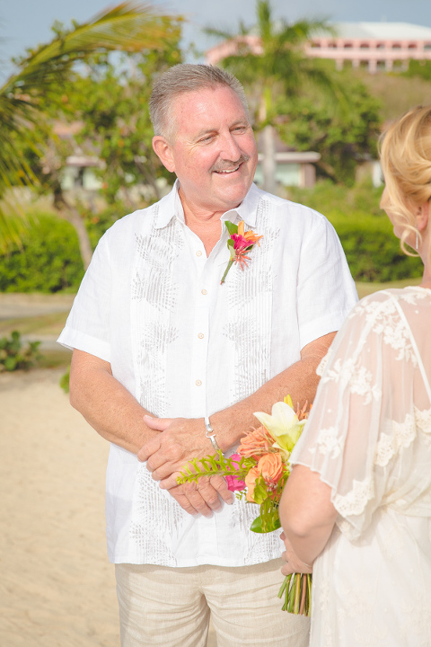 St. Croix groom smiling at bride on beach