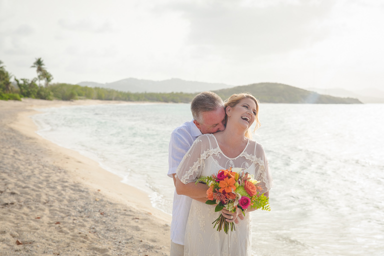 St. Croix groom holding laughing bride with bouquet bouquet