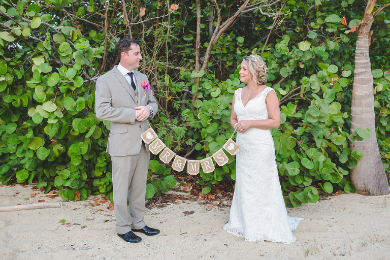 St. Croix bride and groom holding wedding sign on the beach