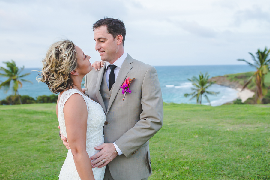 St. Croix bride and groom looking each other in the eyes on a hillside by the beach