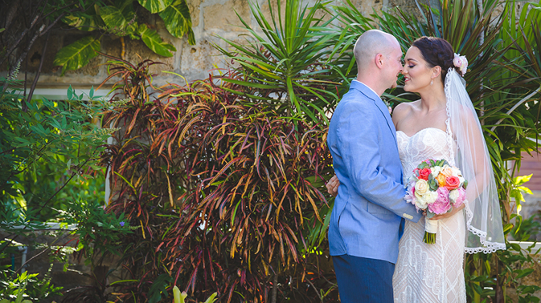 St. Croix Wedding couple kissing in front of tropical plants.