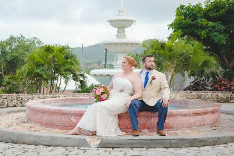 St. Croix bride and groom sitting on water fountain edge