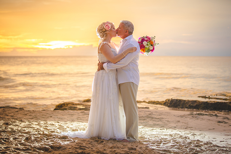St. Croix wedding couple kissing on beach with amazing orange sunset