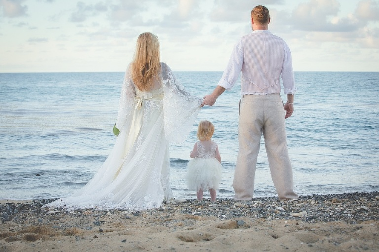St. Croix bride and groom with child holding hands on beach